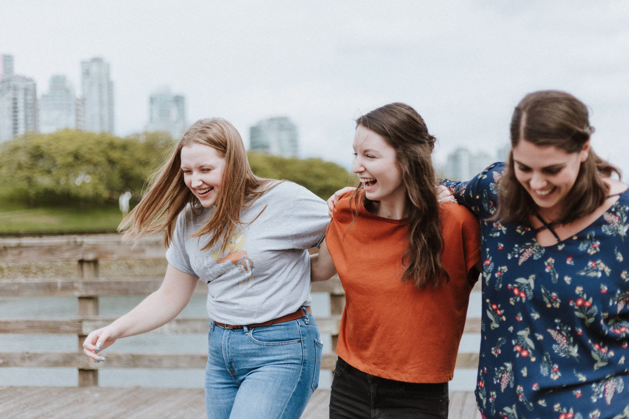 Three girls link arms and laugh