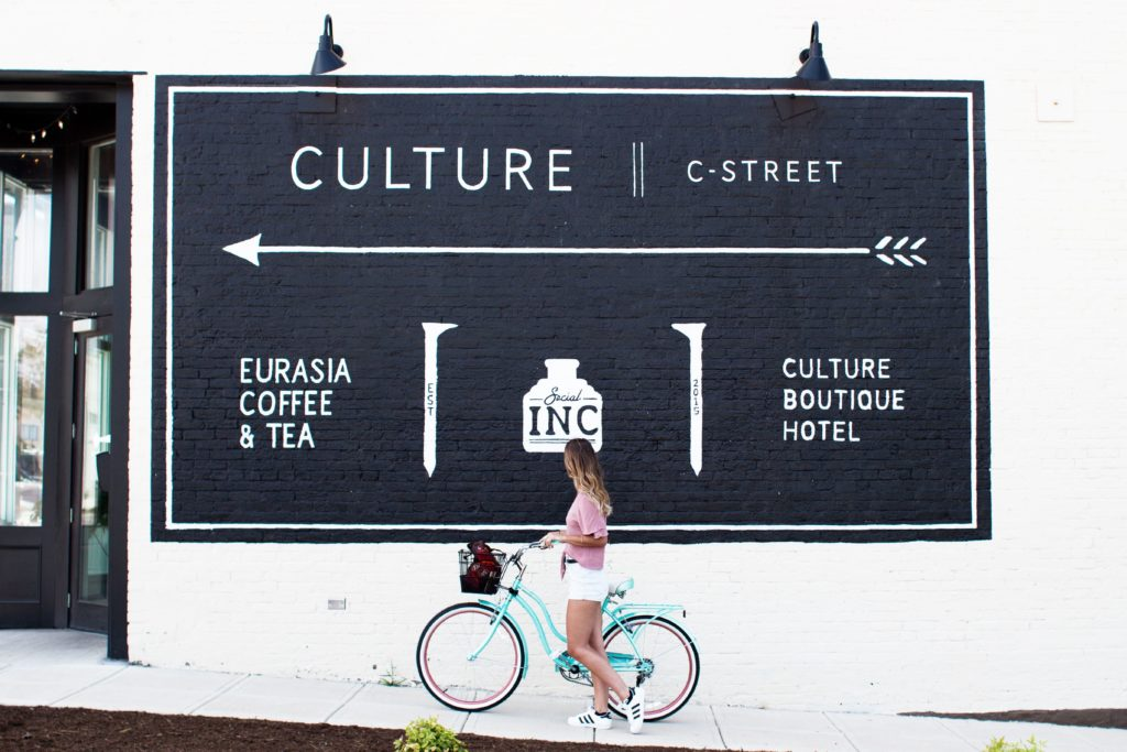 """Woman riding a bike in front of a billboard reading """"Culture"""""""
