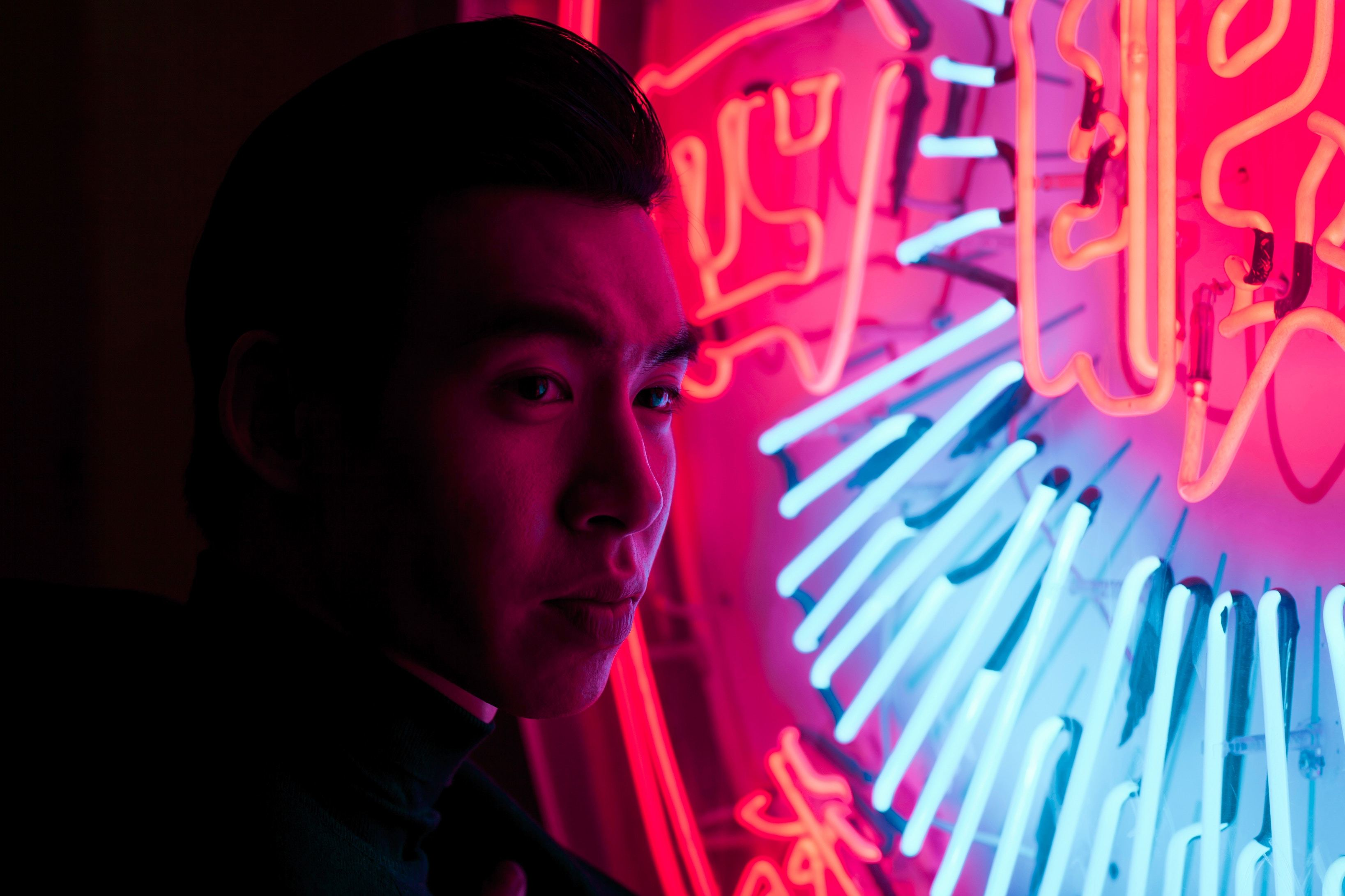 Young Chinese man with neon sign