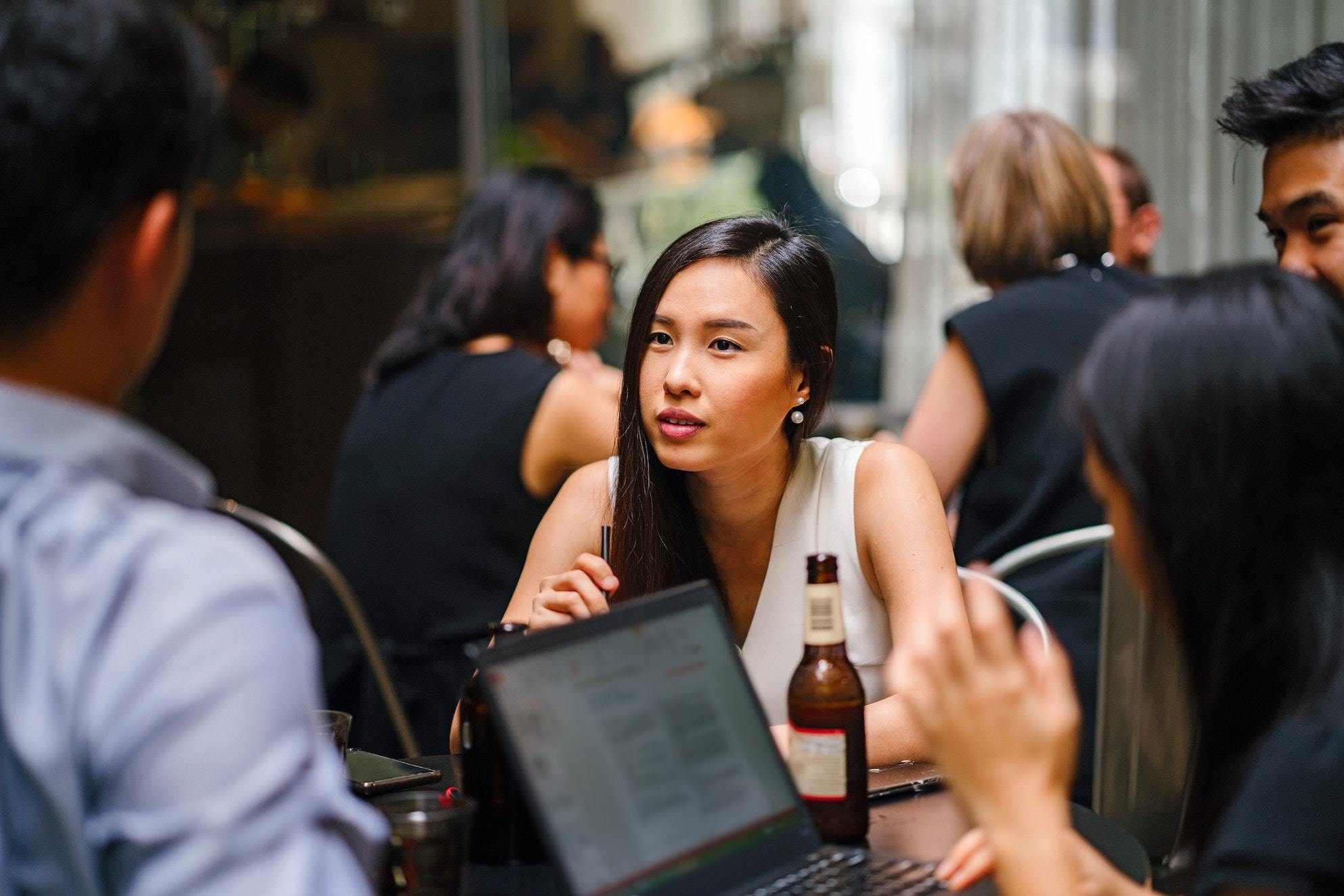 Group of colleagues at a bar with a laptop