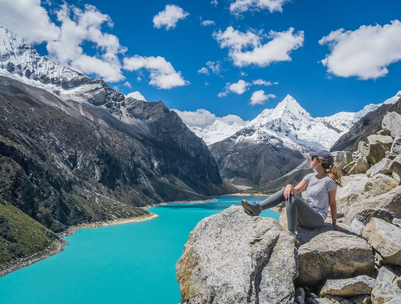 woman sits on rock ledge overlooking green lake surrounded by mountains