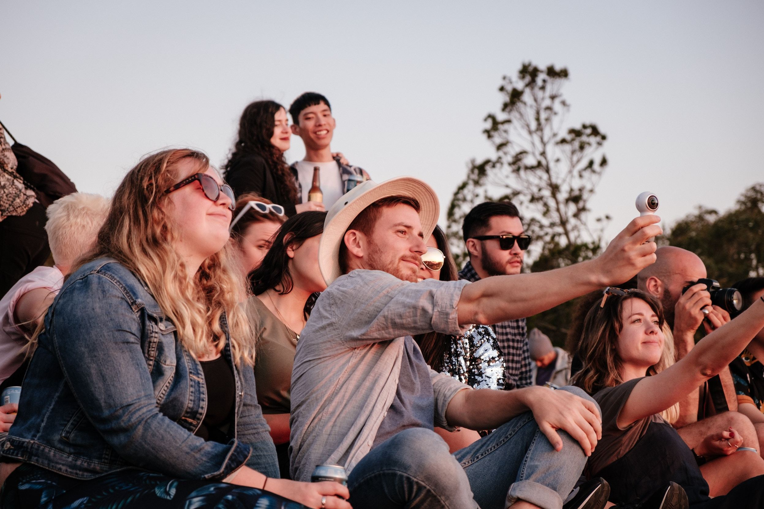 group of people sitting in nature recording a sunset