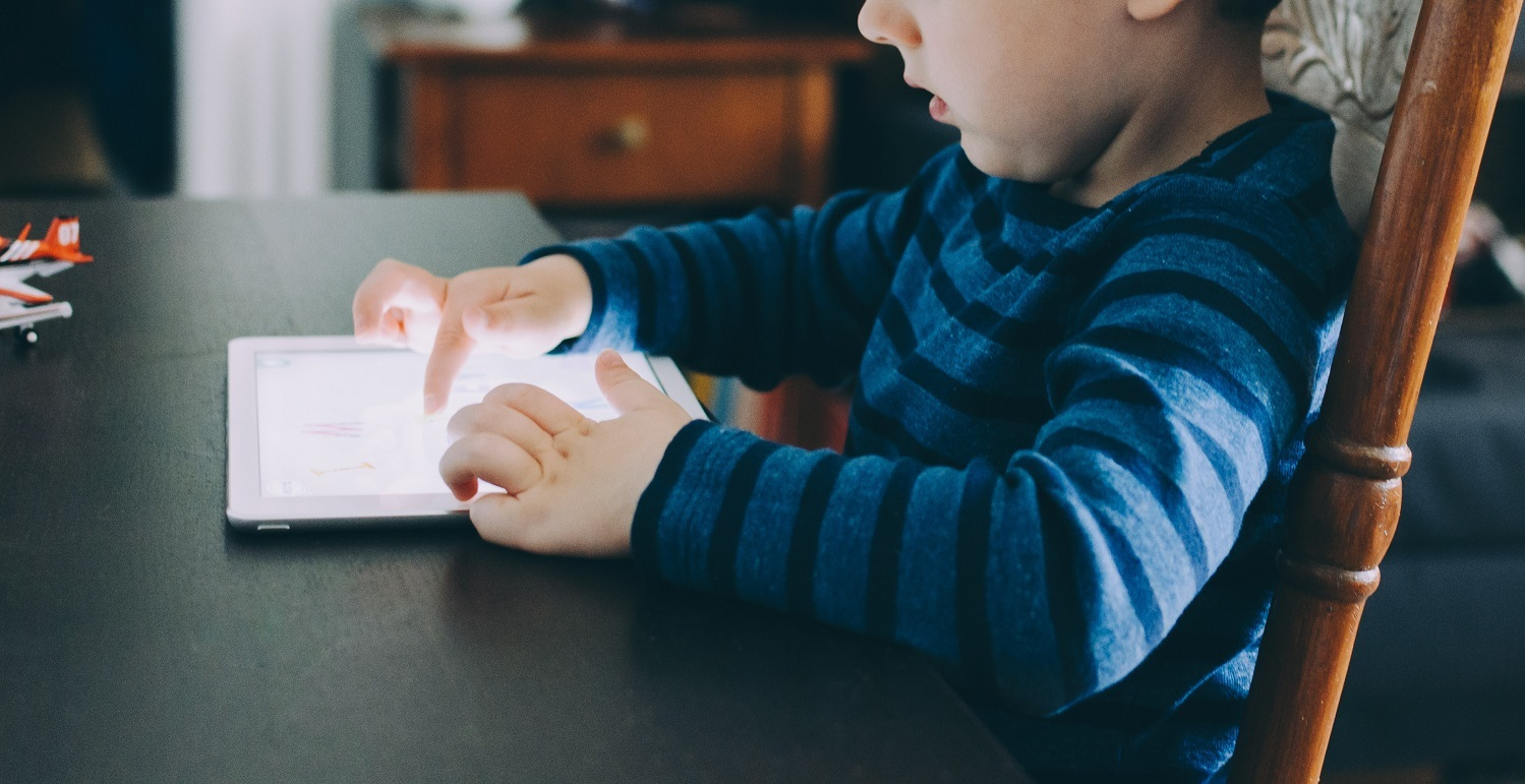 boy plays with tablet at kitchen table