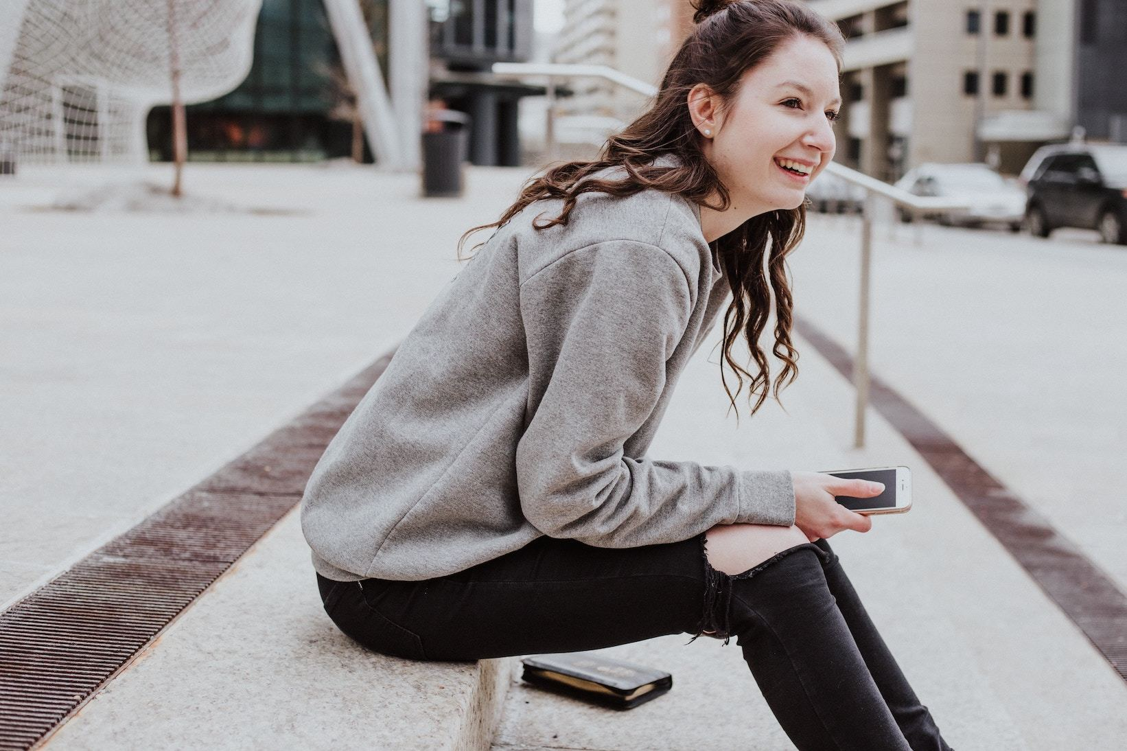 Woman sitting on step, holding smartphone and smiling