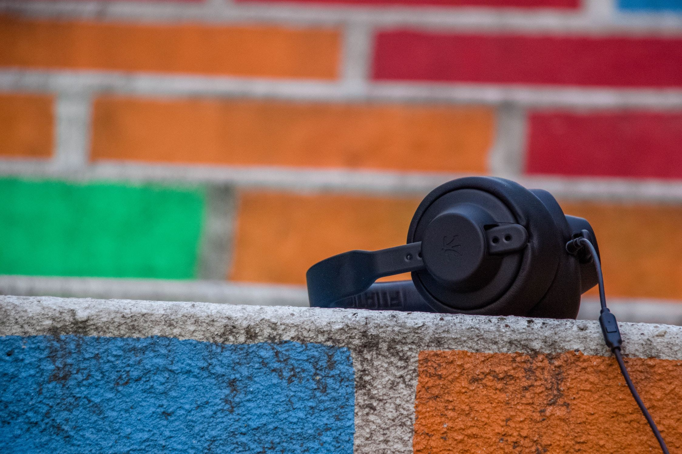 Headphones in front of a painted brick wall