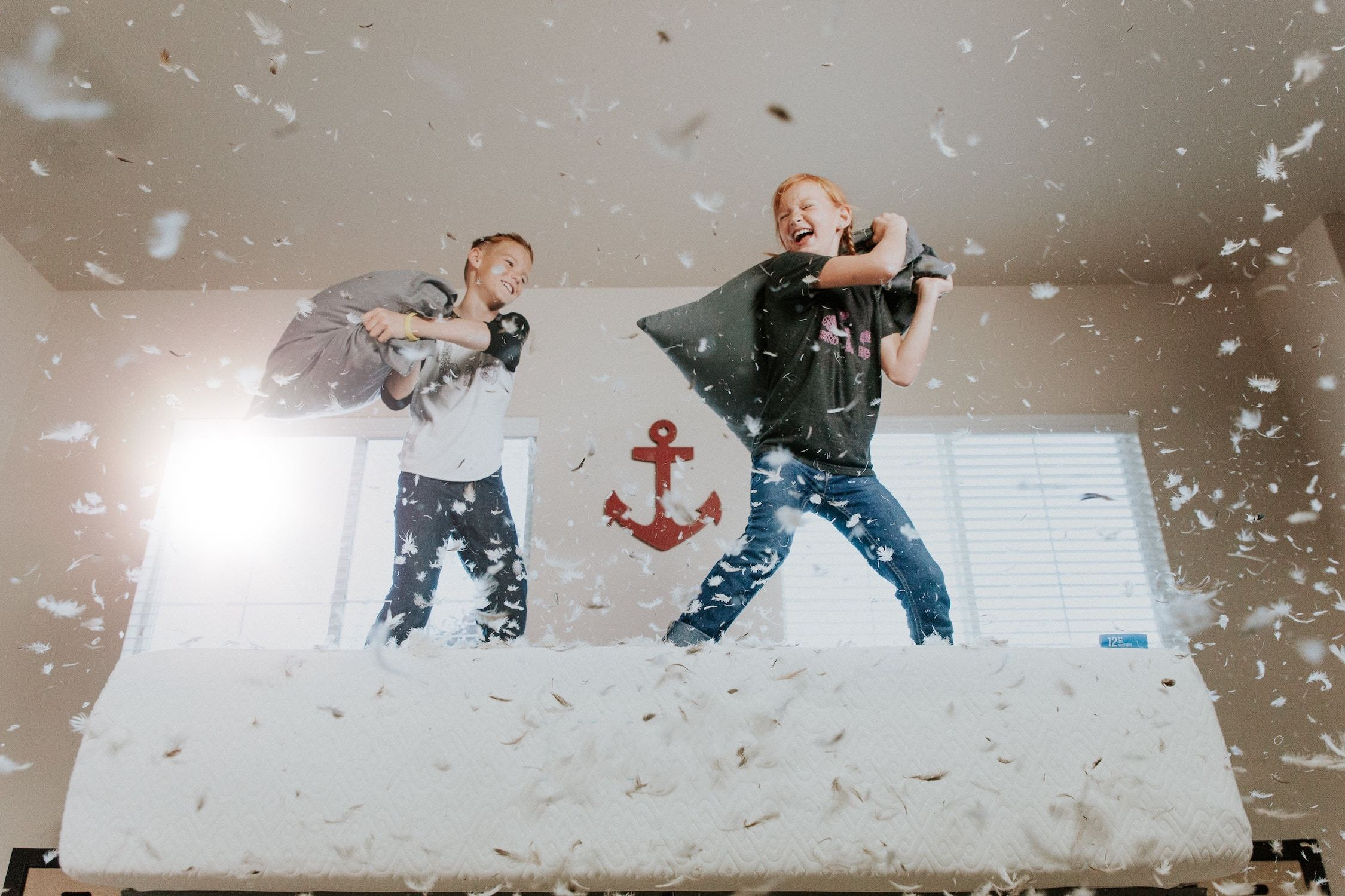 Two children having a pillow fight