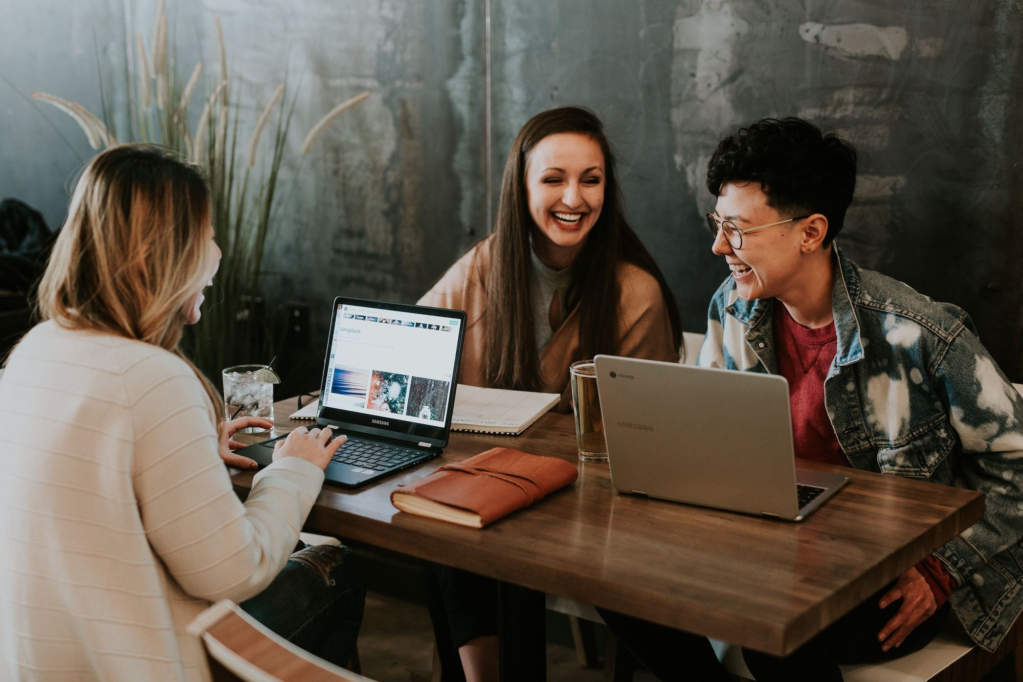 three women at a work table laughing