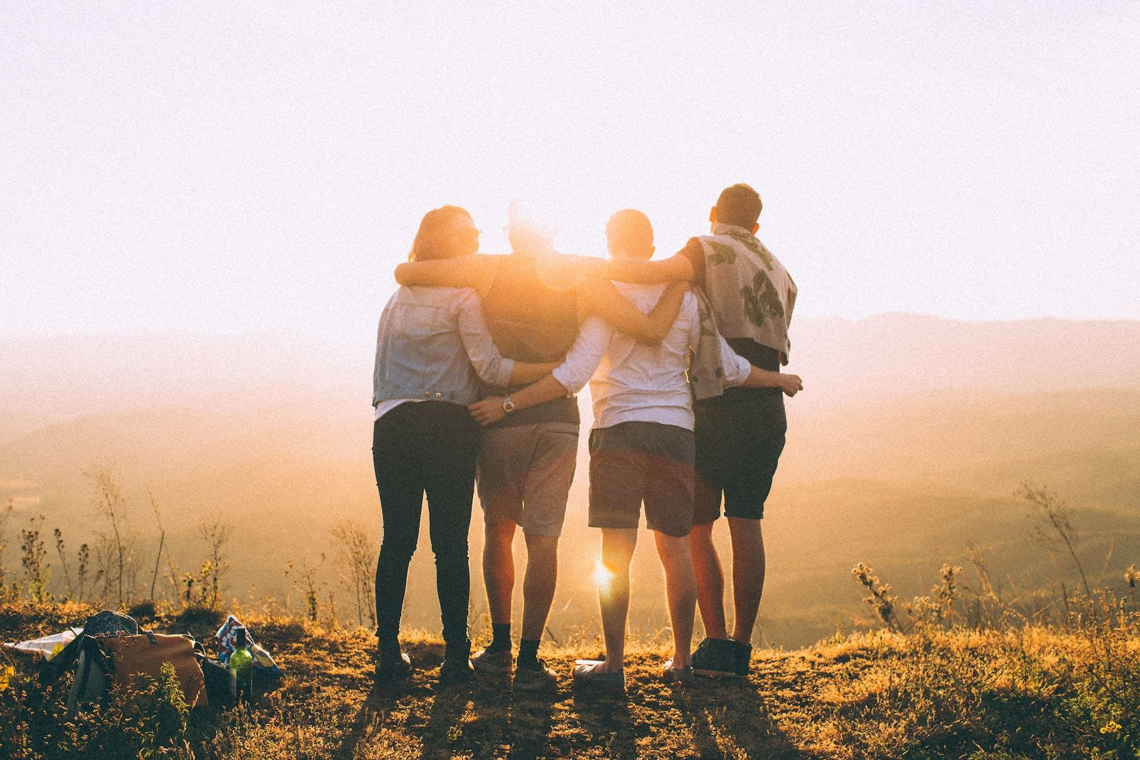 Four people with arms around each other