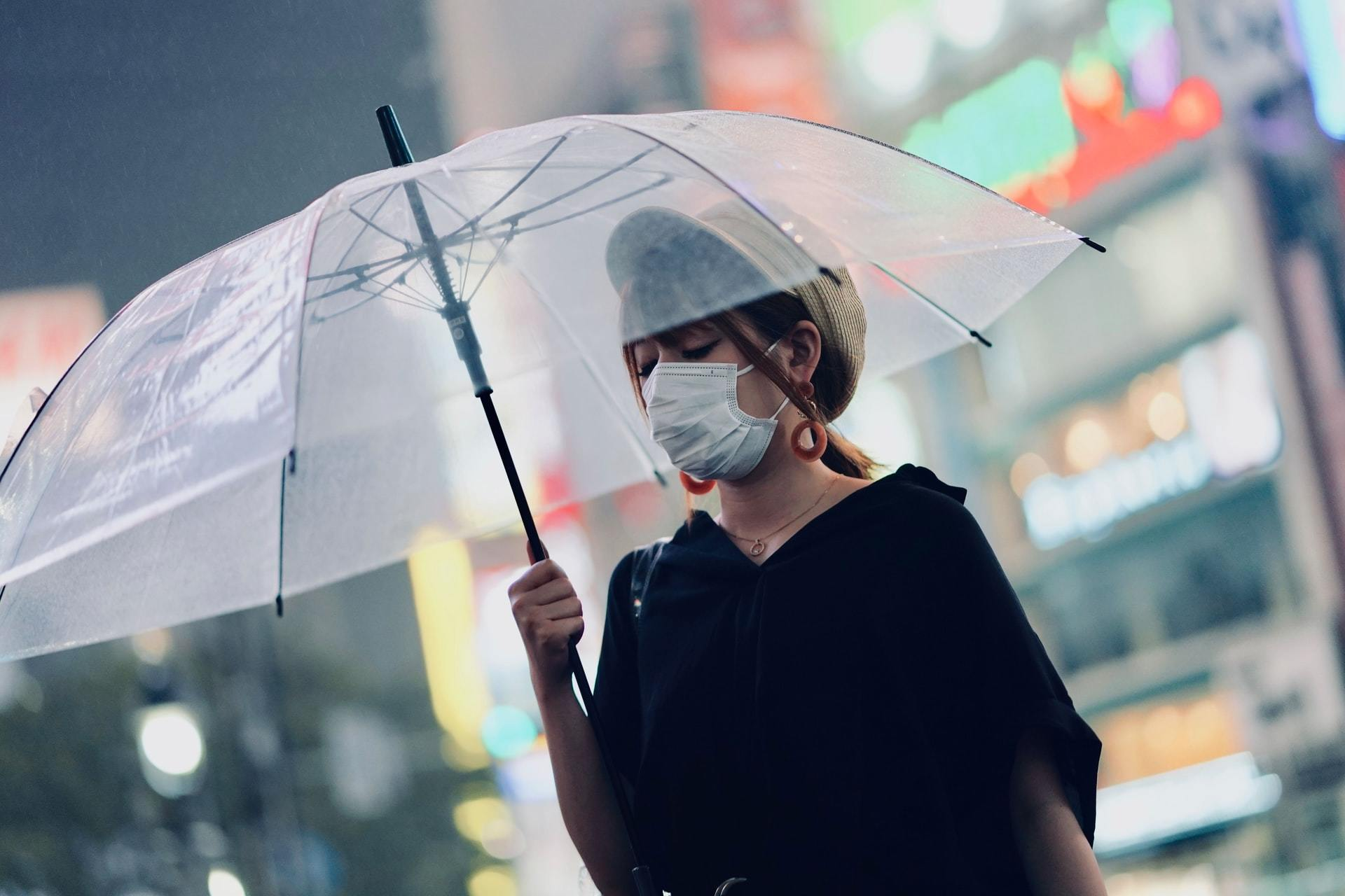 Woman in mask walks with umbrella during coronavirus
