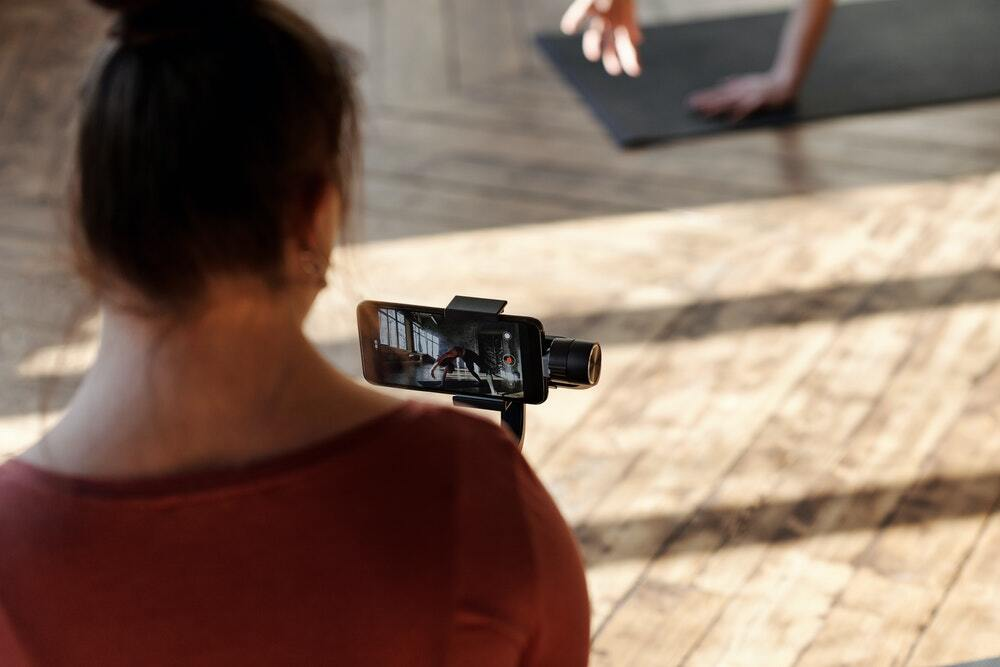 A woman records a video for a content marketing campaign using her iPhone.