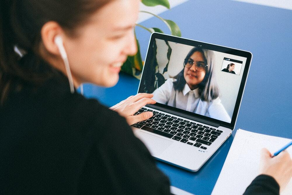 Two women have a video call to discuss their content marketing strategy.