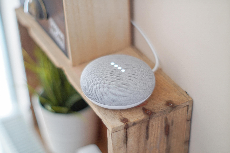 A grey smart speaker on a wood shelf