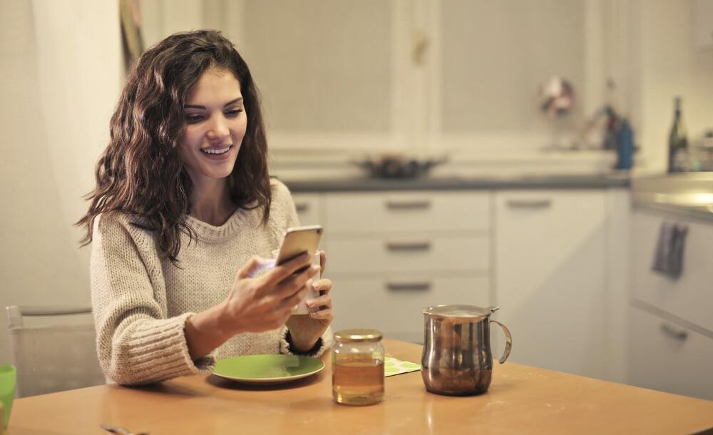 A woman wearing a sweater drinks tea and browses content marketing stories on her smartphone.