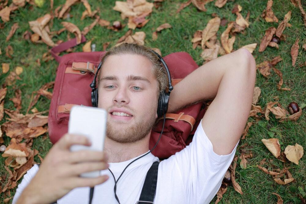 Man lying on grass listening to a podcast and reading its transcript.
