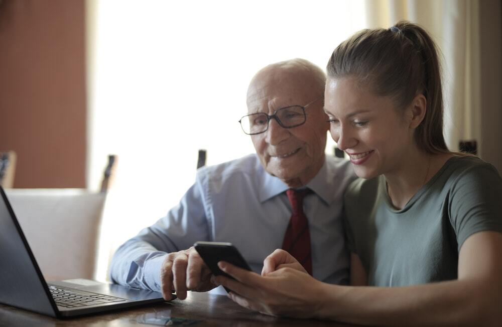 A positive elderly man and a smiling young woman watching a quality content marketing video.