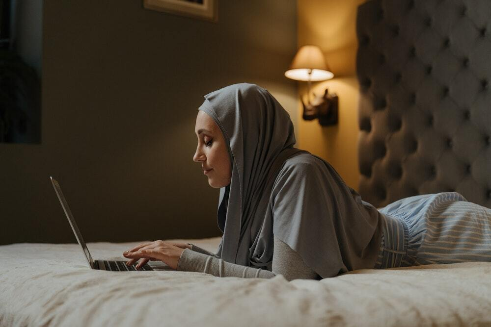 A woman in a hijab sitting on a bed watching a live content marketing webinar.