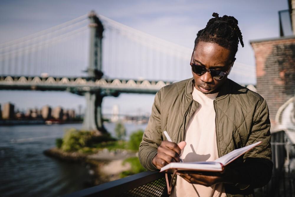 Man writes in planner in front of bridge