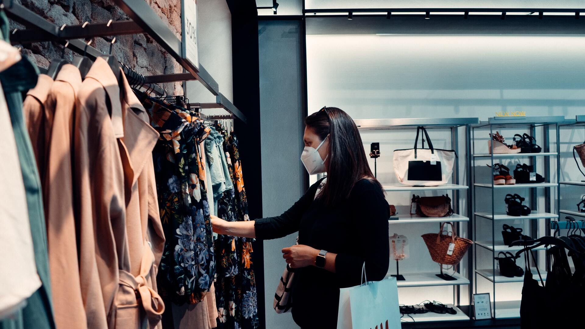 woman shops in clothing store with mask during covid
