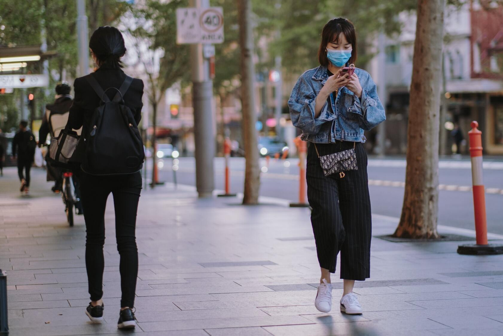 Woman in mask reads phone while practicing social distancing