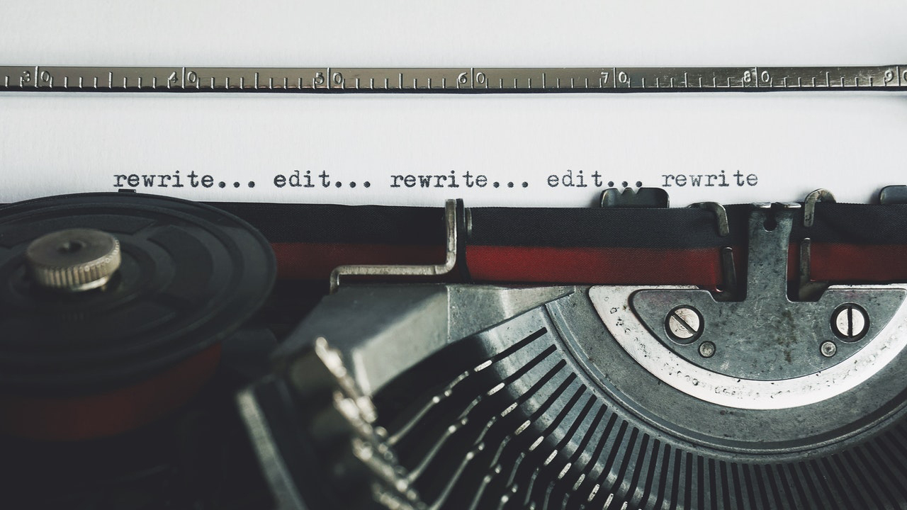 a close-up of a typewriter with the words rewrite and edit repeated multiple times