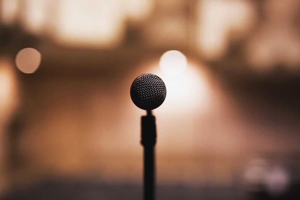 A microphone surrounded by a hazy, warmly lit background.