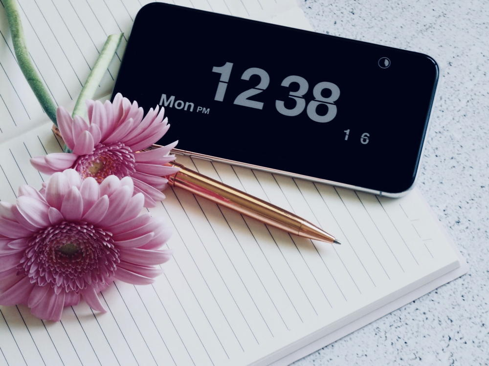 Smartphone with a large clock display placed alongside a brass pen, a blank notepad, and pink Gerbera daisies on a granite desktop.